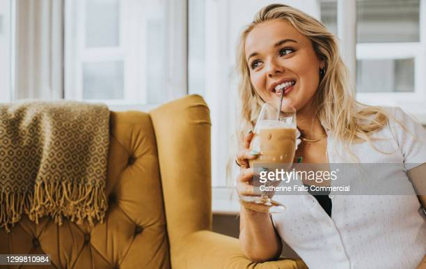 smiling woman sips a cold drink with a metal straw - touching stock pictures, royalty-free photos & images