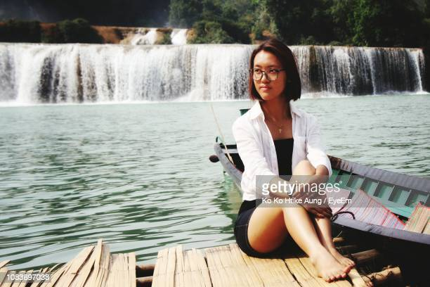 smiling woman sitting against waterfall - ko ko htike aung stock pictures, royalty-free photos & images