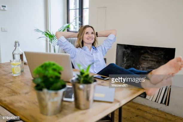 Smiling woman sitting at desk at home with feet up