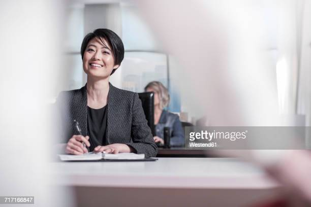 Smiling woman sitting at desk in city office