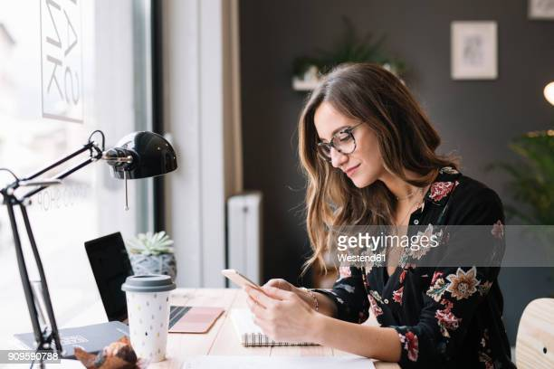 Smiling woman sitting at desk in tattoo studio looking at cell phone