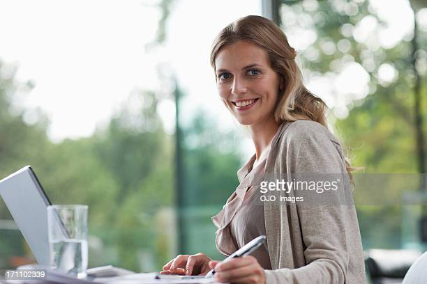 Smiling woman sitting at desk with paperwork