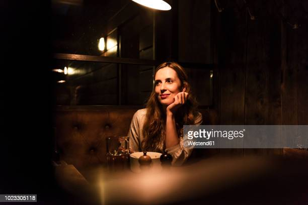 smiling woman sitting at dining table looking sideways - daten stockfoto's en -beelden