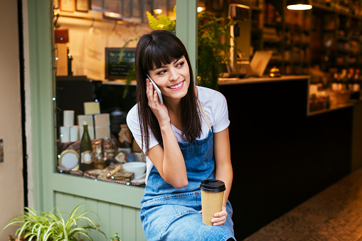 Smiling woman sitting at entrance door of a store talking on cell phone - gettyimageskorea