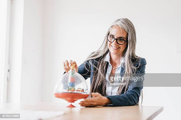 Smiling woman sitting at table playing with spinning top