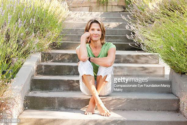 smiling woman sitting barefoot on cement steps - legs crossed at ankle stock pictures, royalty-free photos & images
