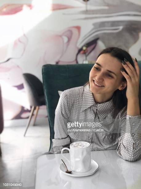 Smiling Woman Sitting By Coffee At Cafe