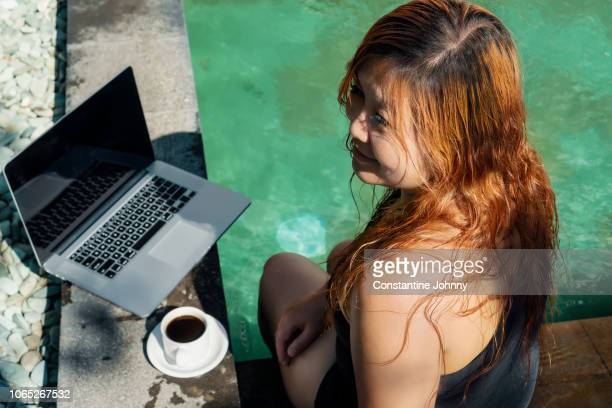 smiling woman sitting by swimming pool with laptop and coffee - ubud district stock pictures, royalty-free photos & images