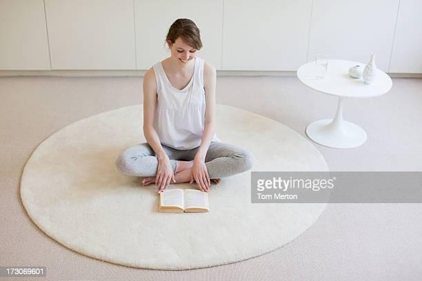Souriant femme assise Assis en tailleur sur le tapis avec livre de lecture
