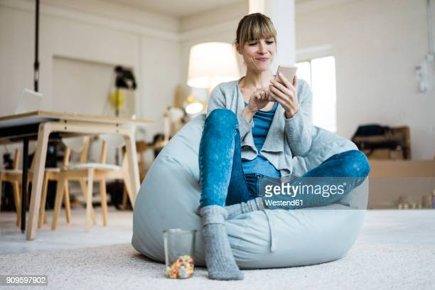smiling woman sitting in beanbag using cell phone - food and drink stock pictures, royalty-free photos & images