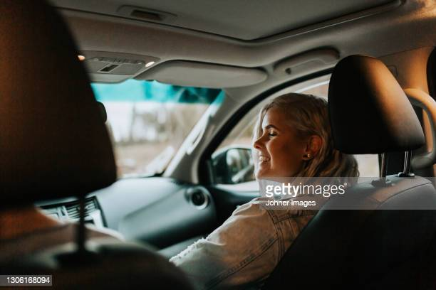 smiling woman sitting in car - västra götaland county stock pictures, royalty-free photos & images
