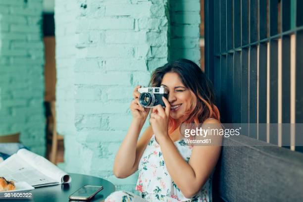 smiling woman sitting in coffee shop taking pictures with camera - one young woman only stock pictures, royalty-free photos & images