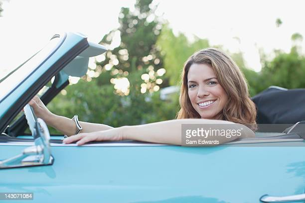 Smiling woman sitting in convertible