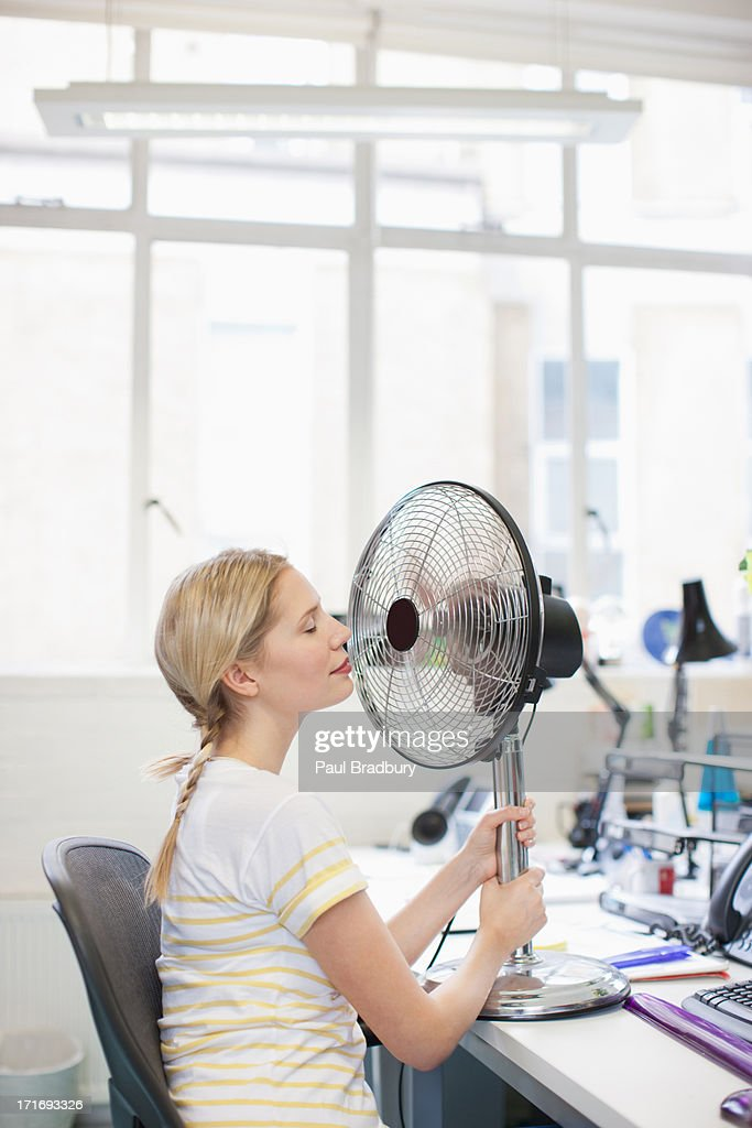 Smiling woman sitting in front of fan in office : Stock Photo