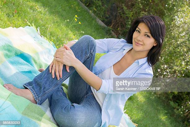 smiling woman sitting in garden on blanket - une seule femme d'âge moyen photos et images de collection