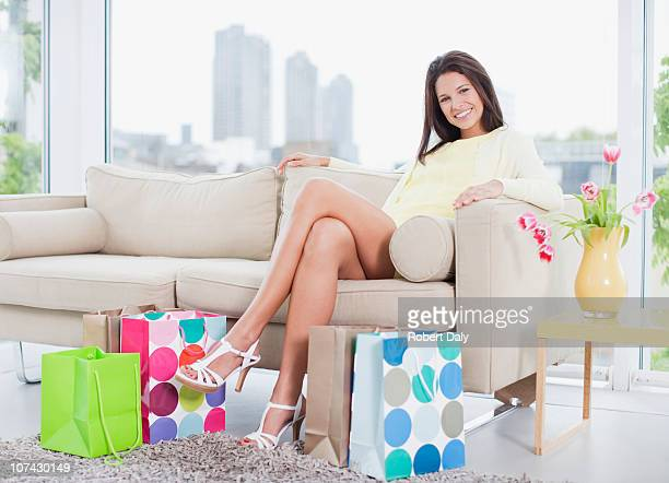 smiling woman sitting in living room with shopping bags - cross legged stock pictures, royalty-free photos & images