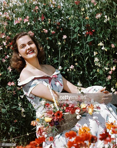 Smiling woman sitting in meadow holding basket of flowers, Los Angeles, California, 1949.