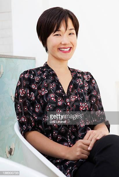 笑顔でモダンな椅子に座る女性