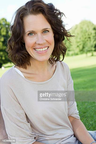 Smiling woman sitting in park