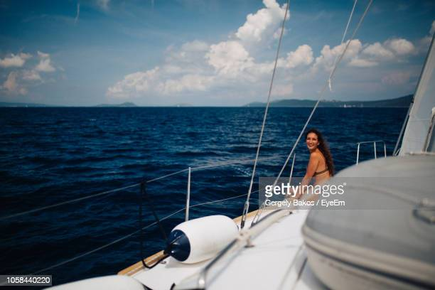 Smiling Woman Sitting In Yacht Sailing On Sea
