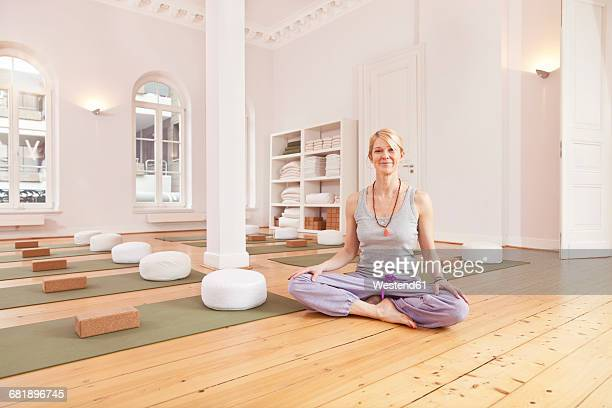 smiling woman sitting in yoga studio - yoga teacher stock pictures, royalty-free photos & images