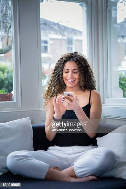 smiling woman sitting near window texting on cell phone - tracksuit bottoms stock pictures, royalty-free photos & images