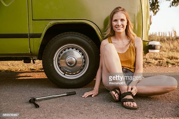 smiling woman sitting next to a torque wrench at van - puncturing stock pictures, royalty-free photos & images