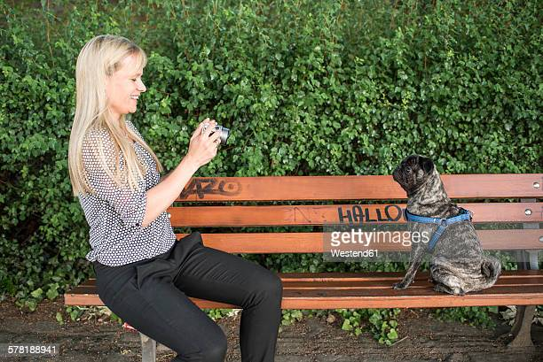 Smiling woman sitting on a bench taking a photo of her pug