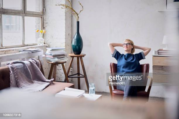 smiling woman sitting on arm chair in loft looking through window - sofa stock-fotos und bilder