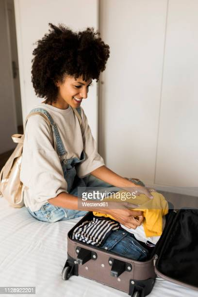smiling woman sitting on bed with suitcase - packing stock pictures, royalty-free photos & images