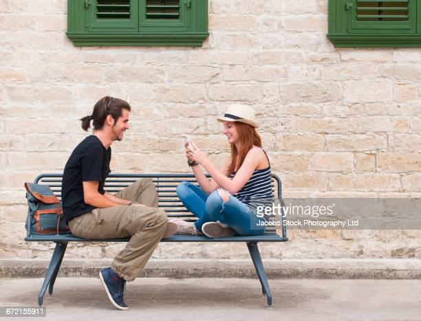 smiling woman sitting on bench photographing man with cell phone - bench stock pictures, royalty-free photos & images