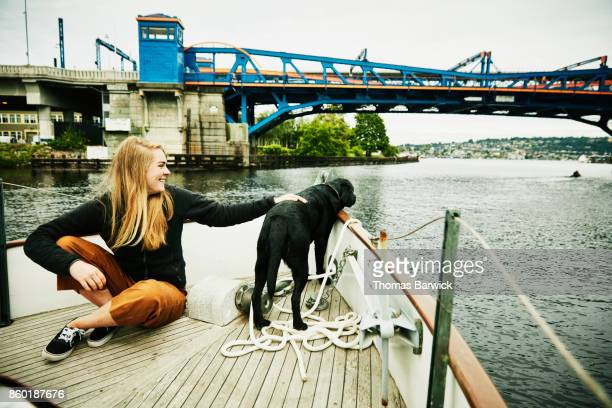Smiling woman sitting on bow of boat cruising through canal  petting dog
