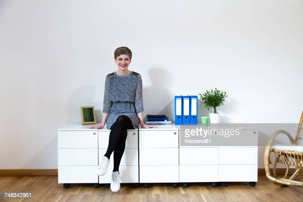 Smiling woman sitting on cabinet in office