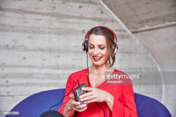 Smiling woman sitting on chair listening to music from walkman