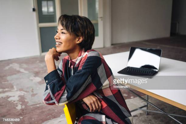 Smiling woman sitting on chair with laptop on table