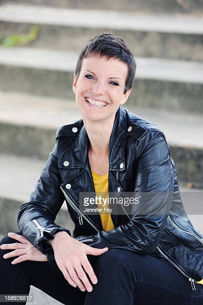 smiling woman sitting on city steps - one mid adult woman only stock pictures, royalty-free photos & images