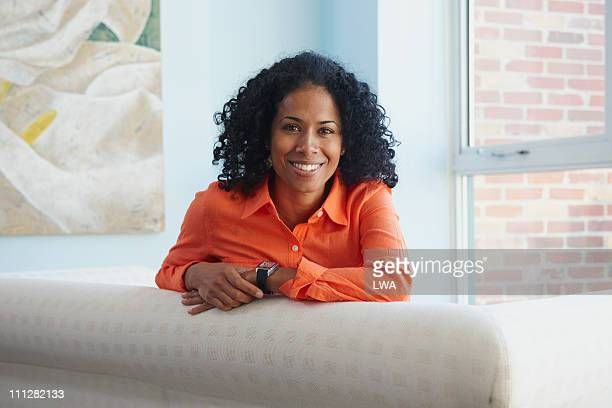 smiling woman, sitting on couch - mid adult stock pictures, royalty-free photos & images
