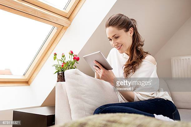 Smiling woman sitting on couch using digital tablet