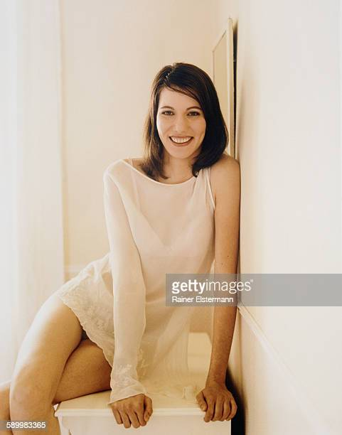 smiling woman sitting on furniture - see thru nightgown stock photos and pictures