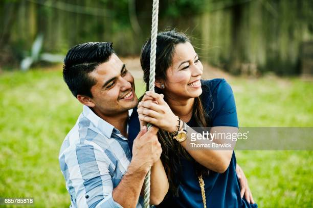 Smiling woman sitting on husbands lap on swing during backyard party