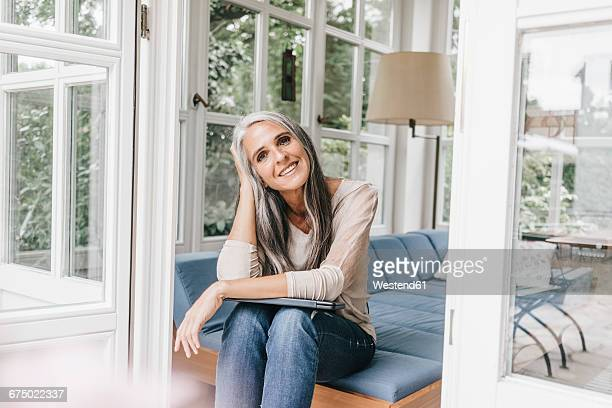 Smiling woman sitting on lounge in winter garden