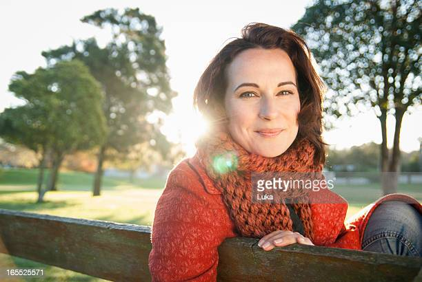 Smiling woman sitting on park bench