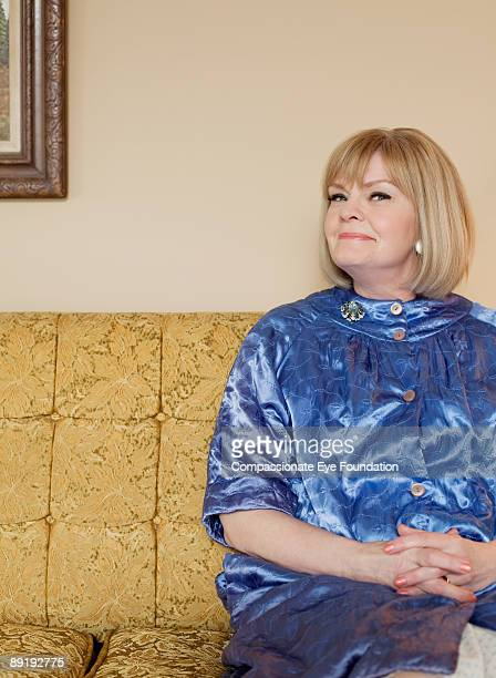 """smiling woman sitting on patterned couch - """"compassionate eye"""" stockfoto's en -beelden"""