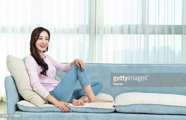 femme de sourire s'asseyant sur le sofa - manches longues photos et images de collection