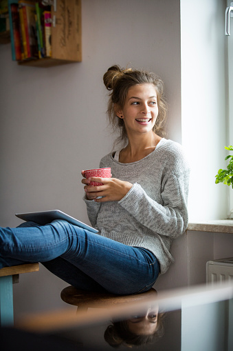 Smiling woman sitting on stool with cup and tablet - gettyimageskorea