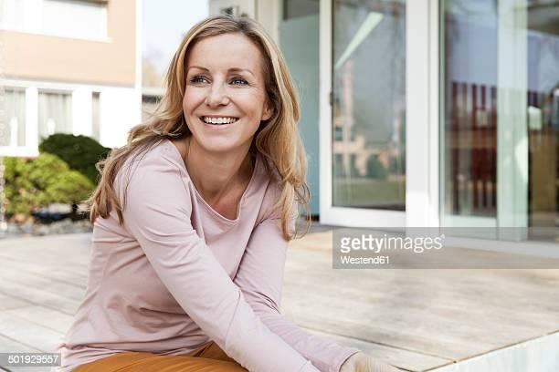smiling woman sitting on terrace of residential house - in den vierzigern stock-fotos und bilder