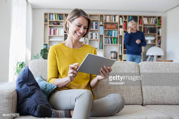 Smiling woman sitting on the couch using digital tablet while her husband telephoning in the background