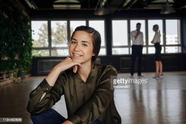 smiling woman sitting on the floor in office with two people in background - 顎に手をやる ストックフォトと画像