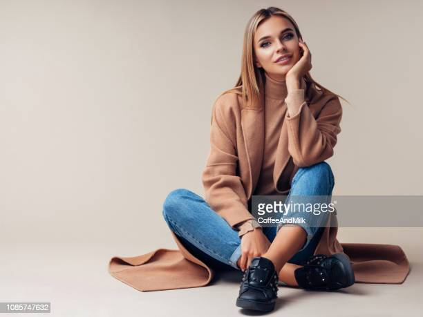 smiling woman sitting on the floor - fashion stock pictures, royalty-free photos & images