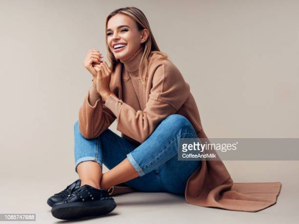smiling woman sitting on the floor - brown shoe stock photos and pictures